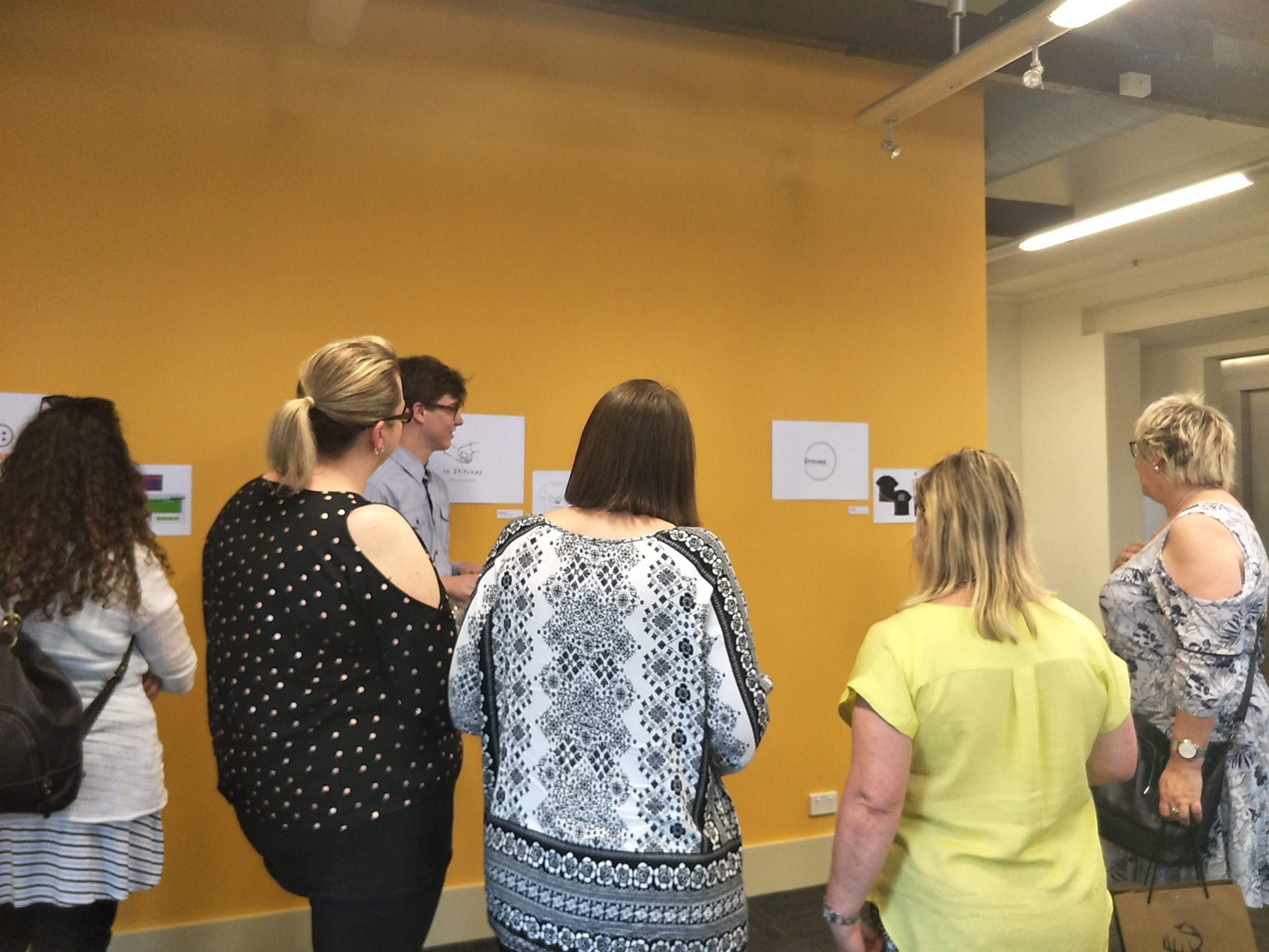 People looking at student work displayed in the Freerange Future office space.