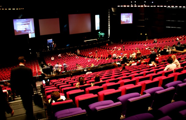 A theatre with red seats with people filing in to sit down