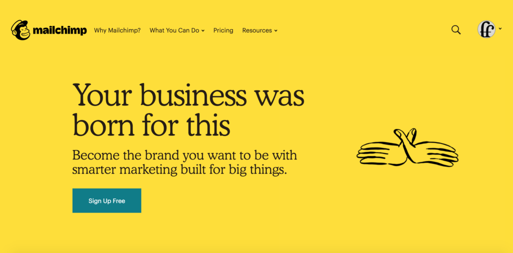 The Mailchimp home page. The tagline 'Your business was born for this' is visible, followed by the subtitle, 'Become the brand you want to be with smarter marketing built for big things.' and a CTA button, 'sign up for free' below. There is a sketch of a to hands mimicking a bird with spreaded wings to the right of the text.